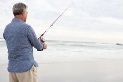 Senior man fishing in sea Royalty Free Stock Photos