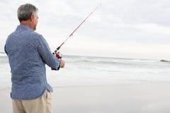 Senior man fishing in sea. Facing away from camera Royalty Free Stock Photos