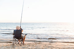 Senior man fishing at sea side stock photos