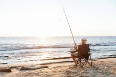 Senior man fishing at sea side stock photo