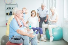 Senior man after fitness classes. Tired senior men sitting on a gym ball with group of elderly people after fitness classes royalty free stock photography