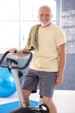 Senior man on fitness cycle smiling. Senior man exercising on fitness cycle, smiling Stock Photography