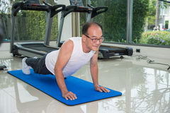 Senior man fitness exercising by doing push ups in the fitness center Stock Image