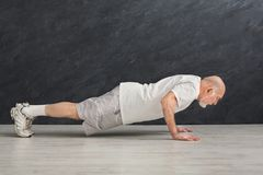 Senior man fitness workout, push ups or plank. Senior man workout in fitness club. e view on mature caucasian guy making plank or push ups exercise, black Royalty Free Stock Image