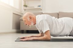 Senior man fitness workout, push ups or plank. Senior man workout at home. e view on mature caucasian guy making plank or push ups exercise. Active lifestyle and Royalty Free Stock Photos