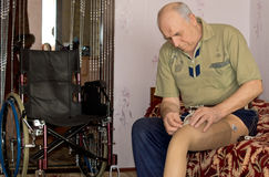 Senior man fitting his prosthetic leg. To his stump following an amputation due to an injury or disease as he sits on the edge of his bed at home Royalty Free Stock Image