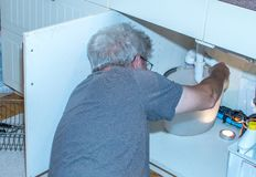 Senior man fixing a leaking pipe under the sink stock photo