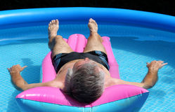 Senior man floating on a lilo Royalty Free Stock Photography