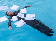 Senior man floating among papers in water Royalty Free Stock Images