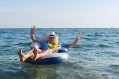 Senior man floating in sea Royalty Free Stock Photos
