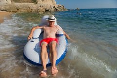 Senior man floating in sea Stock Image