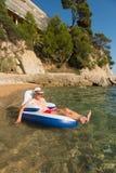 Senior man floating in sea Stock Photos