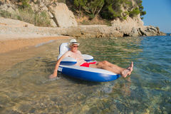 Senior man floating in sea Stock Images
