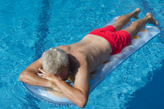 Senior man floating on water Stock Photos