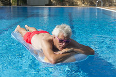 Senior man floating on water Stock Photos