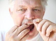 Senior man flosses teeth Royalty Free Stock Photo
