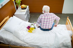 Senior man with flowers in hospital stock photos