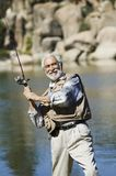 Senior man fly fishing Stock Image