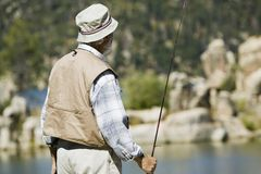 Senior man fly fishing. Middle-aged man fly fishing Stock Photography