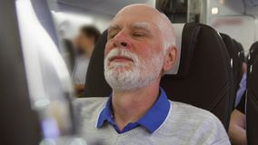 Senior man flying in airplane in daytime. Tired by jet lag male relaxing near window during turbulence