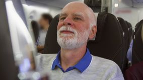 Senior man flying in airplane in daytime. Tired by jet lag male relaxing near window during turbulence. Senior man flying in airplane in daytime. Tired by jet stock video