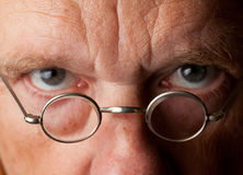 Senior man with focus on glasses. Portrait of a senior male with the focus on magnifying glasses and the eyes are blurred to suggest poor vision Royalty Free Stock Image
