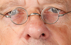 Senior man with focus on glasses. Portrait of a senior male with the focus on magnifying glasses and the eyes are blurred to suggest poor vision Royalty Free Stock Photos