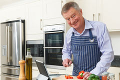 Senior Man Following Recipe On Digital Tablet Stock Photography