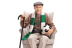 Senior man with a football and a scarf sitting in an armchair. Isolated on white background stock photography