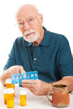 Senior Man Forgot to Take Medicine. Confused senior man can't remember whether or not he took his pills.  Could be early sign of Alzheimer's Disease or dementia Stock Photos