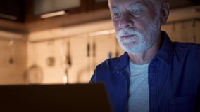 Senior man freelancer using laptop at night from home-office. Overworked businessman working hard stock footage