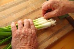 Man prepares scallions stock photos