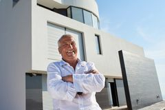 Senior man in front of modern home Stock Photo