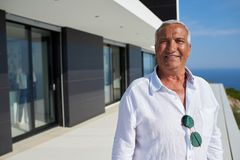 Senior man in front of modern home Royalty Free Stock Image