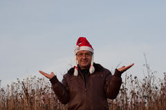 Senior man in funny santa hat with pigtails with raised hands Stock Photos