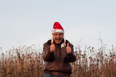 Senior man in funny santa hat with pigtails shows two hands thumbs up Royalty Free Stock Image