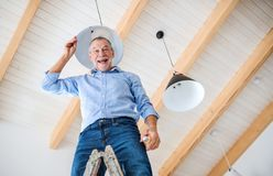 A senior man furnishing new house, having fun. New home concept. A low angle view of senior man furnishing new house, having fun. A new home concept stock photos