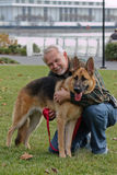 Senior Man and German Sheperd Dog. Senior man with his German Shepherd companion stops in the greenspace while sightseeing along the Potomac waterfront in Stock Photos