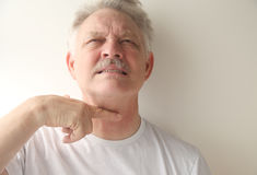 Senior man gestures with finger across throat Royalty Free Stock Images