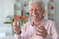 Senior man  gestures at home. Portrait of a happy senior man gestures at home Stock Photography