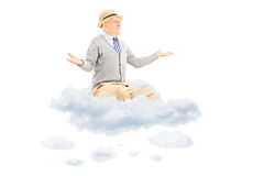 Senior man gesturing with hands seated on a cloud. Senior gentleman gesturing with hands seated on a cloud isolated on white background Stock Photography