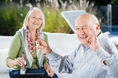 Senior Man Gesturing Okay While Playing Rummy With. Portrait of happy senior men gesturing okay while playing rummy with women at nursing home Royalty Free Stock Photo