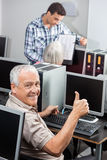 Senior Man Gesturing Thumbs Up At Computer Desk. Portrait of senior men gesturing thumbs up at computer desk in classroom Stock Images
