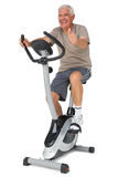 Senior man gesturing thumbs up on stationary bike Stock Images