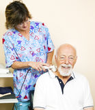 Senior Man Gets Ultrasound. Senior man getting ultrasound therapy for his neck pain Stock Photo