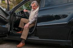 Senior man getting out of car royalty free stock image
