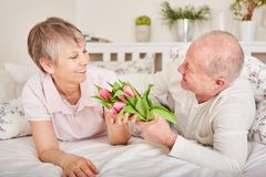Senior man gives flowers to wife. Senior men gives flowers to wife for her birthday or valentine`s day Stock Photo