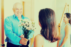 Senior man giving bunch of flowers to woman Royalty Free Stock Images