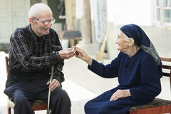 Senior man giving cherry to woman Stock Photo