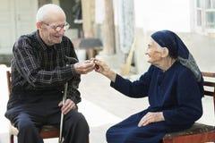Senior man giving cherry to woman Stock Photo